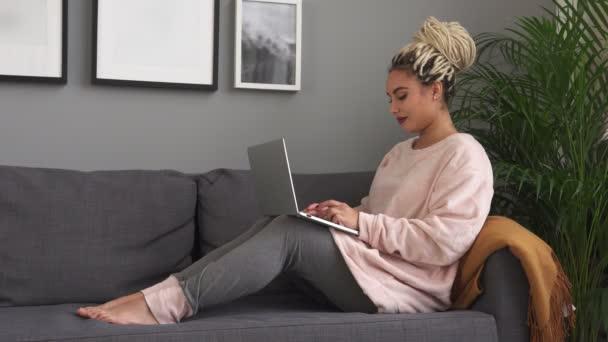 junge schöne Frau arbeitet am Laptop und lächelt auf bequemem Sofa zu Hause