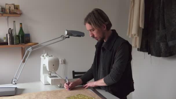 Mann-Designer-Zeichnung kreative Kleidungsschnittmuster während der Arbeit im workshop
