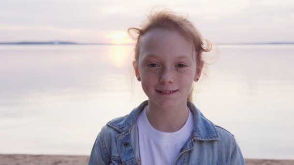 Krásná rusovlasá dívka s pihami na moři při západu slunce