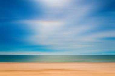 blurred sandy seashore on blue sky background