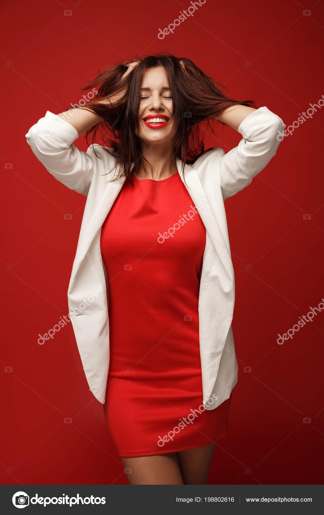 modische fröhliche mädchen einem roten kleid und einer