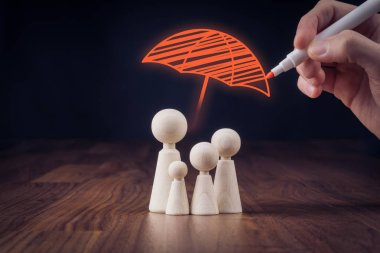 Wooden figurines representing family and hand drawing umbrella, symbol of insurance