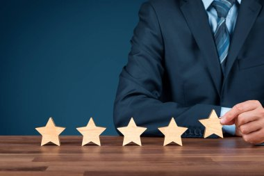 Increase rating, evaluation and classification concept. Businessman sitting behind a table and add fifth wooden star.