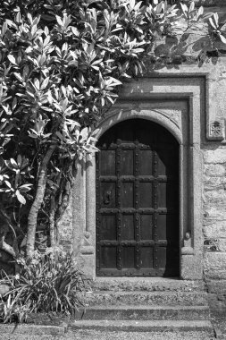 Beautiful old Victorian mansion entrance door surrounded by plants and tree in black and white