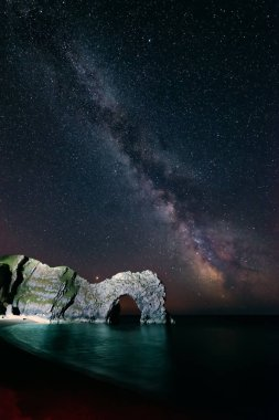 Stunning colorful image of Milky Way galaxy over sea landscape in Dorset England