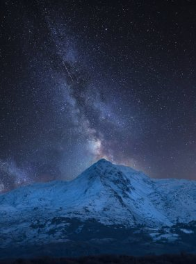 Stunning vibrant Milky Way composite image over landscape of Mount Snowdon and other peaks in Snowdonia National Park