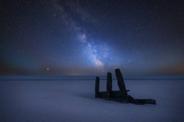 Stunning vibrant Milky Way composite image over landscape of empty beach and old groyne