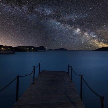 Stunning vibrant Milky Way composite image over landscape of jetty on coastline in Mediterranean Sea