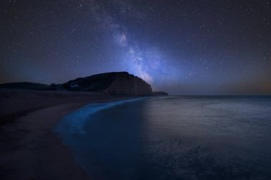 Stunning vibrant Milky Way composite image over landscape of long exposure of West Bay in Dorset