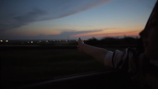 Young woman puts her hand out moving car window,  At night in the countryside.