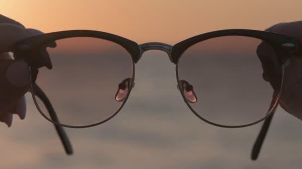 Ženské ruce drží brýle, pozadí modré mořské vody.