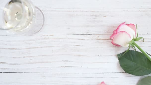 Cinemagraph - Glass with white wine and rose flower on wooden background.  Motion Photo.