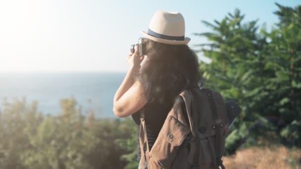 Šťastné ženy turista s batohem. Žena dělat obrázky s retro fotoaparát při cestování