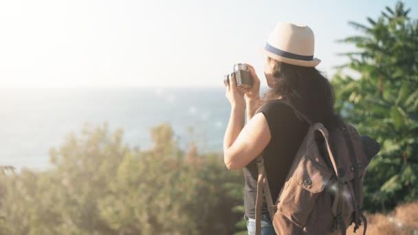 Šťastné ženy turista s batohem. Žena dělat obrázky s retro fotoaparát při cestování .