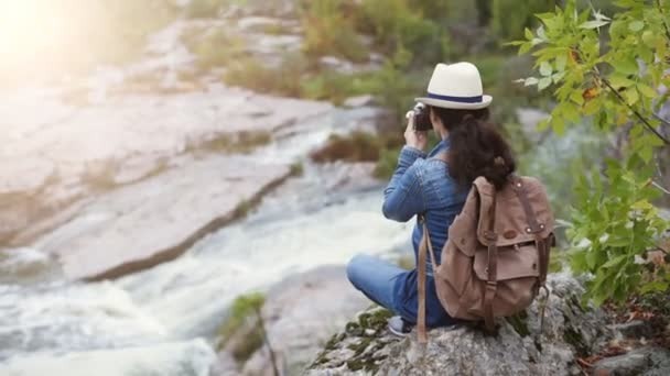 Woman making pictures with a camera while traveling. Natural canyon with view of the mountain river. Concept of travel.