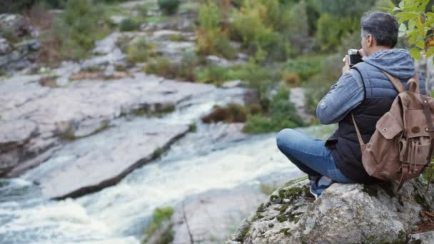 Man making pictures with a camera while traveling. Natural canyon with view of the mountain river. Concept of travel.