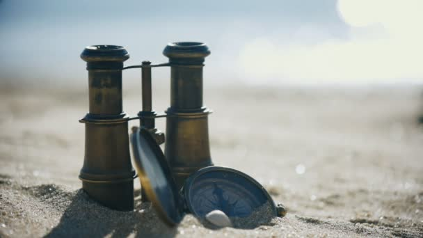 Old vintage compass and binoculars on the sand beach. Travel navigation concept .