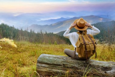 Woman traveler with backpack enjoying sunset on peak of mountain. Concept of travel.