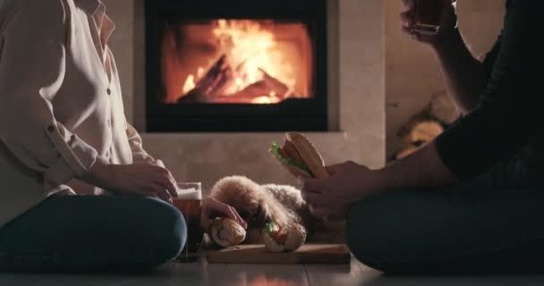 Junges Paar haben romantische Abendessen mit Hot Dogs und Bier über Kamin Hintergrund. Romantisches Konzept.