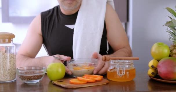 Dospělý člověk jíst zdravé ovesné vločky po cvičení.