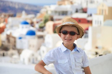 Portrait of young blonde boy in hat on the streets of Oia, Santorini, Greece
