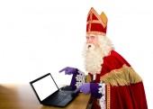 Sinterklaas zeigt auf Laptop. isoliert auf weißem Hintergrund. holländischer Charakter des Weihnachtsmannes oder des Heiligen Nikolaus