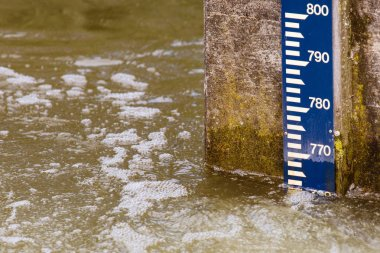 water level pole on a concrete wall in river