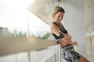 Fitness girl relaxing at the gym by window