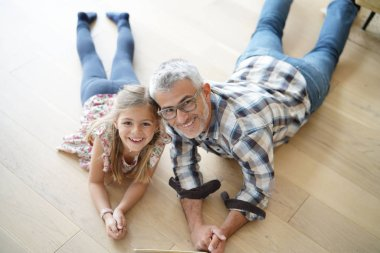 Upper view of little girl with daddy laying on wooden floor