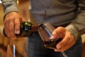 Az ember szolgálja a vörös bor, a pincészet borkóstolás