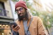 Portrét bokovky chlap na ulici spojené s smartphone