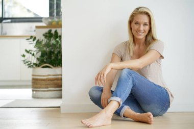Beautiful blond woman sitting on floor against white wall