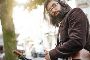 Hipster guy in town using headset with smartphone