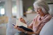 Seniorin liest zu Hause auf Couch
