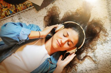 Beautiful young woman with closed eyes listening to music