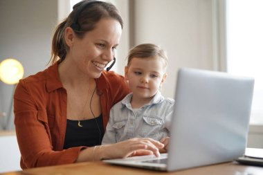 Mother working from home on computer with her young daughter
