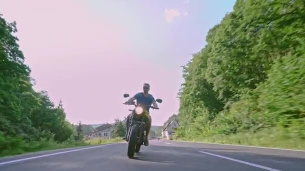 Modern custom scrambler motorbike on a forest road riding - overtaking and carving actions. Having fun driving the empty road on a motorcycle tour journey. 4k Video.