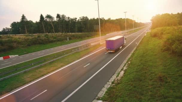 Komerční nákladní automobil s přívěsem nákladní disky přes prázdné silnici. Automobil je bílá a modrá. Slunce svítilo na pozadí