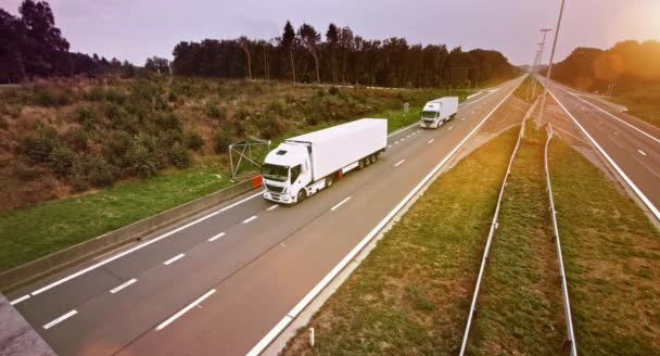 dvě obchodní kamiony s přívěsem nákladní disky přes prázdné silnici. Truck je bílá. Slunce svítilo na pozadí