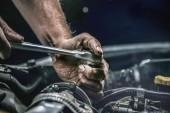 Autószerelő dolgozik autó motor mechanika garázsban. Javítási szolgáltatás. Hiteles közeli lövést.