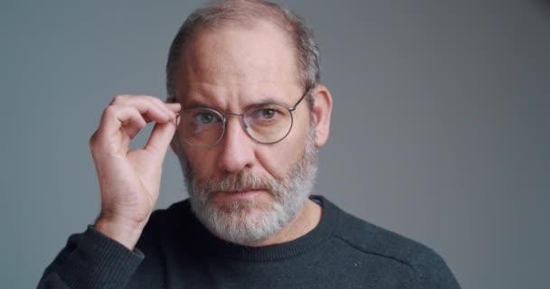 Portrét vousatého dospělého příležitostného obchodníka s brýlemi, které se dívají do kamery