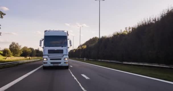 Nákladní vůz s nákladním přívěsem na dálnici. Bílý náklaďák doručuje zboží v časných hodinách ranní-velmi nízký úhel jízdy..