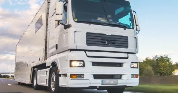 Lastkraftwagen mit Ladeanhänger auf einer Autobahn. White Truck liefert Waren in den frühen Morgenstunden aus - sehr schräge Fahrt durch Nahaufnahme.