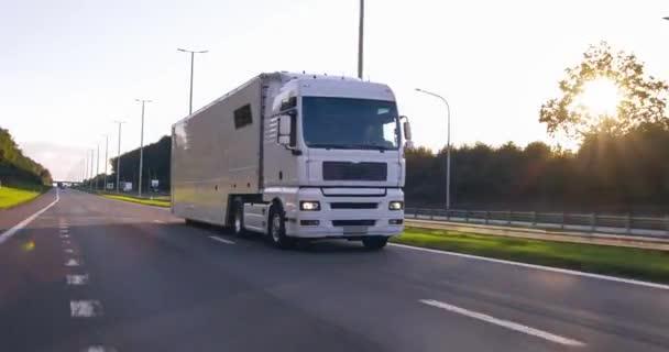 Lastkraftwagen mit Ladeanhänger auf einer Autobahn. White Truck liefert Waren in den frühen Morgenstunden aus - sehr schräge Fahrt durch Nahaufnahme