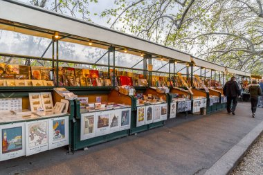 Book and souvenir stands and people shopping along Tiber River i