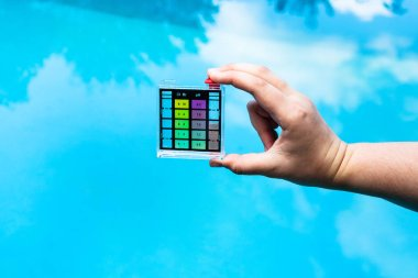 hand holds pH indicator for measure the acidity of water in a swimming pool