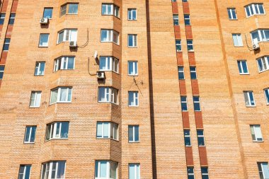 facade of urban brick multi-storey house in Moscow city on sunny summer day