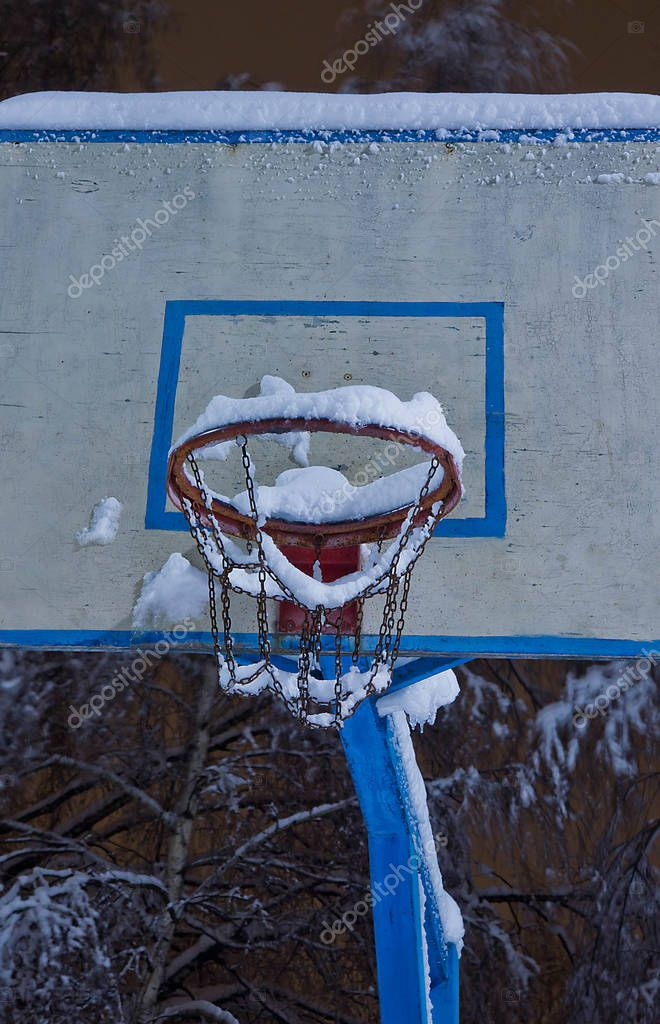 basketball hoop under snow in a city park
