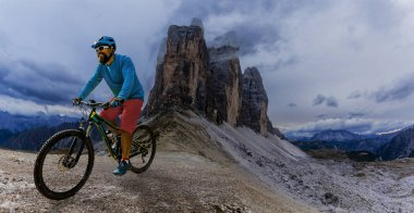 Cycling man riding on bikes in Dolomites mountains and
