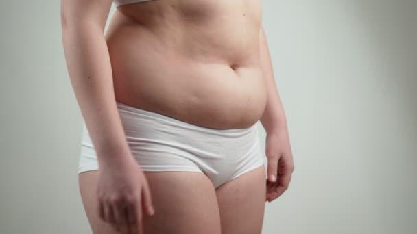 Žena v bílém prádle drží její břišní tuk.